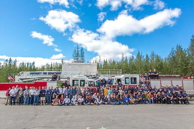 Current and former firefighters with the University Fire Department pose for a group photo during the 50th UFD reunion picnic July 19 at the University Avenue fire station.  Filename: LIF-14-4251-018.jpg