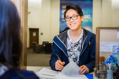 Biology student Jimin Kim fills out paperwork at the Office of the Bursar.  Filename: LIF-16-4906-46-Edit.jpg