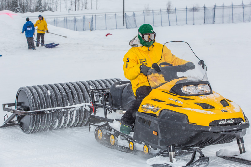 """Student employees and staff members work to groom the big jump on UAF's Terrain Park on a snowy spring afternoon.  <div class=""""ss-paypal-button"""">Filename: LIF-13-3721-27.jpg</div><div class=""""ss-paypal-button-end"""" style=""""""""></div>"""