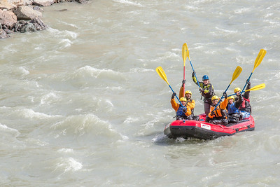 Students and staff members raise their paddles in triumph after navigating a stretch of white water on a raft trip down the Nenana River led by UAF Outdoor Adventures in June, 2014.  Filename: OUT-14-4211-418.jpg