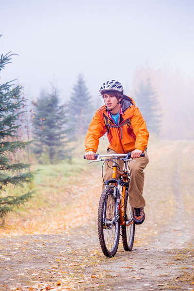 """Mechanical engineering major Adam McCombs rides his bike through the potato field towards campus on a recent foggy morning.  <div class=""""ss-paypal-button"""">Filename: LIF-12-3556-031.jpg</div><div class=""""ss-paypal-button-end"""" style=""""""""></div>"""