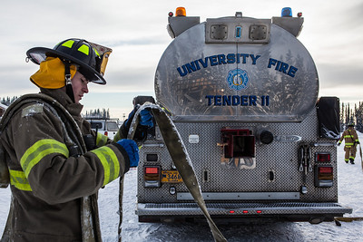 Aaron Stevens rolls a fire hose after filling an outdoor ice rink for children at Ice Alaska's George Horner Ice Park in Feb. 2013.  Filename: LIF-12-3723-111.jpg