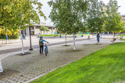 A students walks her bike towards the library on the first day of the fall 2013 semester on the Fairbanks campus.  Filename: LIF-13-3928-3.jpg