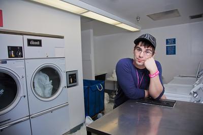 Freshman Robert Doerning takes time to do laundry in Skarland Hall.  Filename: LIF-12-3322-090.jpg