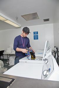 Freshman Robert Doerning takes time to do laundry in Skarland Hall.  Filename: LIF-12-3322-063.jpg