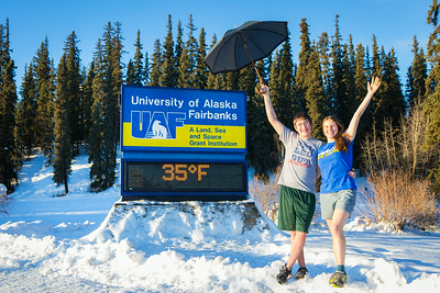 Sporting shorts and a t-shirt in above freezing temperatures in January, Megan Lasselle and Seth Reddell pose for a portrait at the time and temperature sign.  Filename: LIF-14-4047-31.jpg