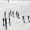 """Students play some ultimate frisbee on the snow-covered field by the SRC on an April afternoon.  <div class=""""ss-paypal-button"""">Filename: LIF-14-4132-6.jpg</div><div class=""""ss-paypal-button-end"""" style=""""""""></div>"""