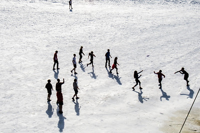 Students play some ultimate frisbee on the snow-covered field by the SRC on an April afternoon.  Filename: LIF-14-4132-6.jpg