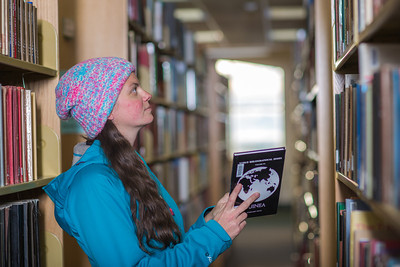 Senior biology major Sarah Dewitt looks through the stacks on the 6th floor of the Rasmuson Library.  Filename: LIF-14-4045-137.jpg