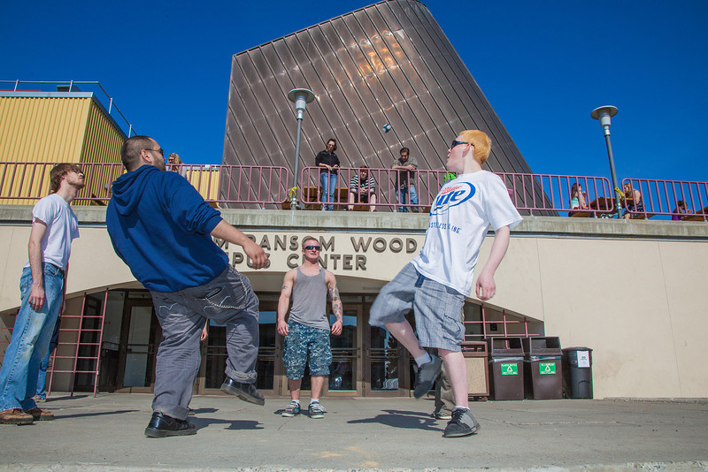 """A group of students play hacky sack outside the Wood Center on campus.  <div class=""""ss-paypal-button"""">Filename: LIF-12-3356-112.jpg</div><div class=""""ss-paypal-button-end"""" style=""""""""></div>"""