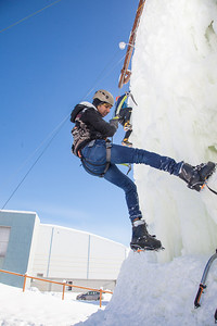 Students take advantage of nice spring weather to try out their climbing skills on the new ice wall near the SRC.  Filename: LIF-12-3321-024.jpg