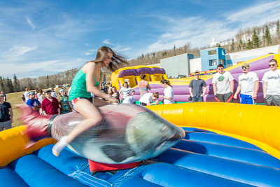 Students took turns getting  knocked off the spinning salmon, one of the many attractions brought to campus during SpringFest Field Day on April 28.  Filename: LIF-14-4168-118.jpg