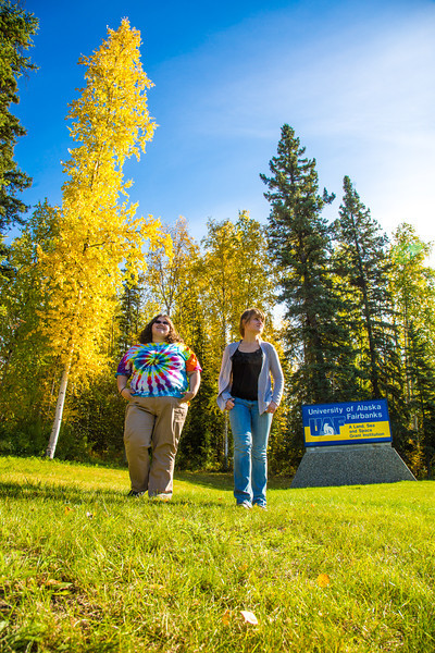 "Grace Amundsen, left, and Kaylie Wiltersen stroll through the grass near the west entrance to campus on a nice fall afternoon.  <div class=""ss-paypal-button"">Filename: LIF-12-3544-016.jpg</div><div class=""ss-paypal-button-end"" style=""""></div>"