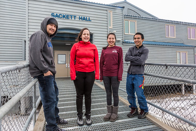 Sackett Hall residents Evan Wassilie from Kasigluk, Wilona Okitkun from Kotlik, Larissa Flynn from Chefornak and Justin Bill from Tooksook Bay pose in front of the residence hall at UAF's Kuskokwim Campus in Bethel on a chilly March evening.  Filename: LIF-16-4859-509-2.jpg