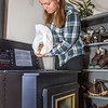 "Emily Russell pours fuel into the newly installed pellet stove in her apartment at UAF's sustainable village housing complex.  <div class=""ss-paypal-button"">Filename: LIF-12-3677-17.jpg</div><div class=""ss-paypal-button-end"" style=""""></div>"