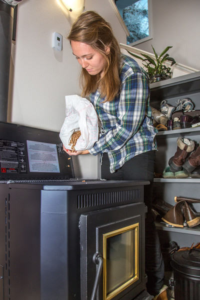 """Emily Russell pours fuel into the newly installed pellet stove in her apartment at UAF's sustainable village housing complex.  <div class=""""ss-paypal-button"""">Filename: LIF-12-3677-17.jpg</div><div class=""""ss-paypal-button-end"""" style=""""""""></div>"""