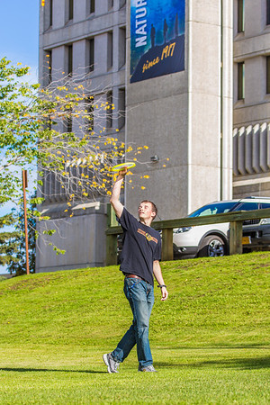 Engineering major Philip White takes time between classes to play with a frisbee on a beautiful September afternoon on the Fairbanks campus.  Filename: LIF-13-3934-52.jpg