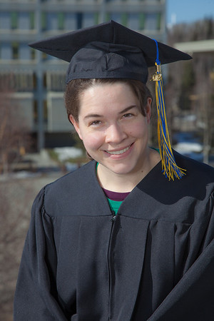 Senior foreign languages major Lindsey Miller poses in her cap and gown on the roof of the Brooks Building on the Fairbanks campus.  Filename: LIF-12-3352-6.jpg