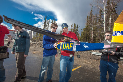 Jeremy Langton, in blue, David Apperson, in red, and other engineering majors tinker with their model airplane before sending it aloft for a test flight over a parking lot on the Fairbanks campus.  Filename: LIF-12-3366-034.jpg
