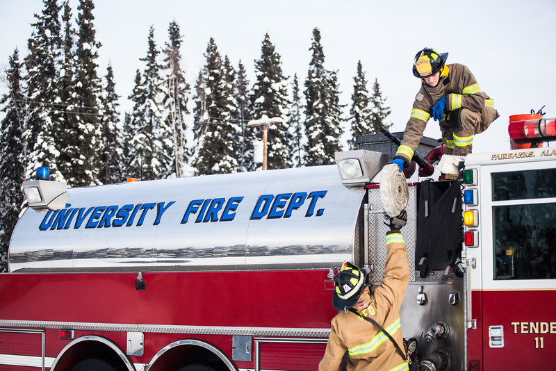 """Spencer McLean hands a rolled up fire hose to Aaron Stevens after filling an outdoor ice rink for children at Ice Alaska's George Horner Ice Park in Feb. 2013.  <div class=""""ss-paypal-button"""">Filename: LIF-12-3723-233.jpg</div><div class=""""ss-paypal-button-end"""" style=""""""""></div>"""