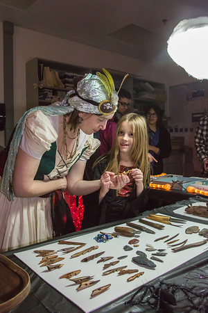 Eight-year-old Rosie Paris handles ancient artifacts with her mom during the Halloween party at the University of Alaska Museum of the North.  Filename: LIF-13-3988-42.jpg