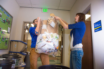 Alex Bergman, left, and Korlyn Bolster  with UAF's Sustainability Office empty a recycling bin outside their office near the Rasmuson Library.  Filename: LIF-13-3689-4.jpg