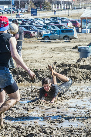 A participant in the 2014 SpringFest mud volleyball bouts gives maximum effort to save a point.  Filename: LIF-14-4167-35.jpg