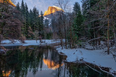 Half Dome illuminated by sunset light reflected on the Merced River  in Winter, Yosmite National Park