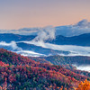 This is a panoramic image of fog in the valley on a clear October morning. The colors are full and popping with reds and oranges in the Appalachian Mountains.