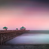 Pier at sunset on Folly Beach, South Carolina. Image taken with a very slow exposure showing the blur of the waves.