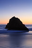 Sea stack silhouette at twilight with crescent moon