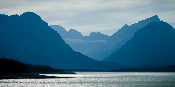 Blue silhouette of mountains with Lake Sherburne in foreground of Glacier National Park.