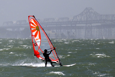 Windsurfing Diva ©  2010 Colleen M. Griffith. All Rights Reserved.  This material may not be published, broadcast, modified, or redistributed in any way without written agreement with the creator.  This image is registered with the US Copyright Office. www.colleenmgriffith.com www.facebook.com/colleen.griffith  Windsurfing and parasailing are amazing in the bay.  Here you can see the San Francisco Bay Bridge in the background.