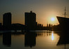 """Sunrise over Oosterdok (East Dock) - the old Amsterdam Harbor - with the sun at the bow of the NEMO Science Center (NEMO in Latin nemo means """"no one"""" and indicates a world between fantasy and reality) - Amsterdam"""