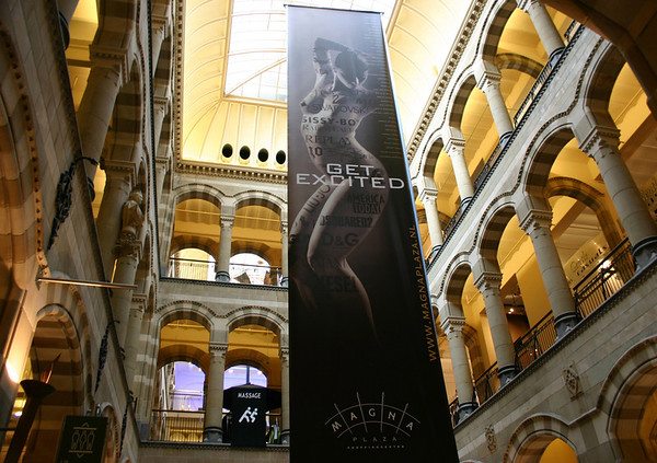 Magna Plaza - built in 1899 - here up the central atrium with three levels of shopping, up to the 19th century glass dome - with the anatomically artistic advertisement banner representing the retailers within the place hanging from above - Amsterdam