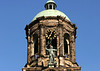 """Oxidized bronze statue of """"Peace"""" - with the sedimentary sandstone bell and clock tower of the Royal Palace (originally the Town Hall of Amsterdam) behind - Amsterdam"""