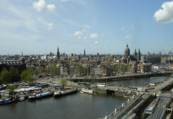 Amsterdam Skyline - Old Center district - from the the Oosterdoc (east dock), at the intersection of Prins Hendrikkade (Prince Henry Wharf or Quay, along the parked busses) and Oosterdokskade (East Dock Wharf) - to the steeples of the Church of St. Nicholas (triple spire, foreground), Westerkerk (Western Church), Nieuwekerk (New Church), Oudekerk (Old Church), and the Koninklijk Paleis (Royal Palace), the oxidized copper dome.