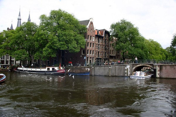 Across the Prinsengracht (Prince's Canal), at the boundary of the Old Center district with the Jordaan district - to the spires of the Posthoornkerk (church) along the horizon - and a canal tour boat passing under a bridge down the Brouwersgracht (Brewers Canal) - Amsterdam