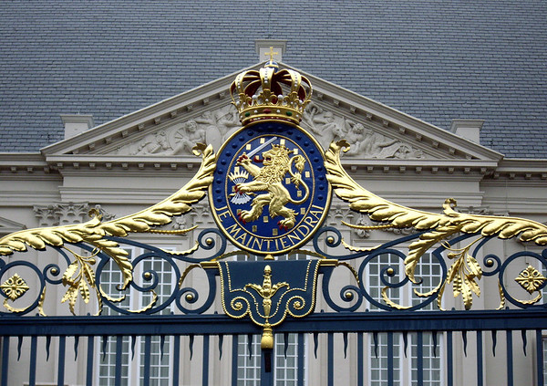 Royal Coat of Arms - for the Kingdom of Netherlands - the escutcheon (a heraldic or blazoned shield), showing the motto: Je Maintiendrai (I Will Maintain) - the lion comes from the coat of arms of the House of Nassau, the sword and sheath of arrows in the lion's paw come from the coat of arms of the States General of the Republic of the United Provinces (17th and 18th centuries), with the 7 arrows representing the 7 provinces - topped with the Imperial Crown - mounted here upon the gate to the Nordeinde Palace - South Holland province
