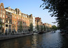 Across the shaded canal - to the day's first sunlight upon the historic merchant warehouses - Amsterdam