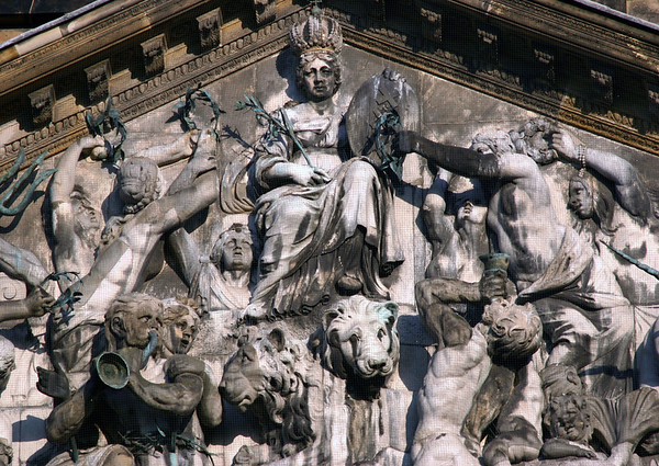 """""""Personification of Amsterdam"""" - the sculpted tympanum bas-relief (Imperial Crown of Austria from Emperor Maximilian I, Habsburg of Austria, with the triple XXX symbol from the coat of arms on the shied, and an olive branch) on the Royal Palace - which has been stained and discolored from the soot, exhaust fumes, acid rain, and bird feces - since its construction in the 17th century - Amsterdam"""