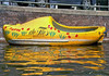 Fiberglass boat replica of the dutch wooden shoe - reflection upon the canal water - Amsterdam