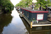 Houseboats along the placid canal water on a canal in the Jordaan district - houseboats were originally developed because of the housing shortage on the approximate 90 islands in the city - Amsterdam