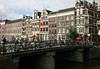 Beyond a canal bridge lined with bicycles - to historic warehouses, some with hoists mounted atop the gable to raise merchandise and goods into the upper storage areas of the narrow warehouses - Amsterdam