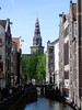 Historic merchant warehouses along the Oudezijds Kolk (Old Side Drain) - is a narrow sluice (water channel) with a (kolk) lock at its end - with the tower and spire of the Old Church beyond the leafing trees - Amsterdam