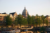 Sunrise light across the Waalseilands Gracht (Island Waal Canal), with its houseboats - beyond the merchant houses - to the dome and twin towers of the St. Nicholas Church - Amsterdam