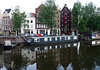Houseboats and merchant warehouses reflections on the canal water - Amsterdam