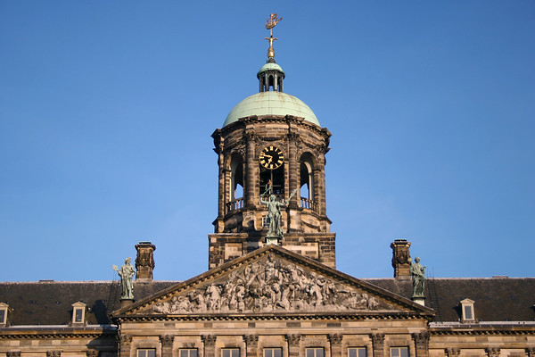 Day's first sunlight upon the sculptured tympanym upon the 66 ft. (20 m) sandstone pediment and sculpted tympanum - beyond the oxidized sculptures - up to the domed cupola, crowned with a cog ship weather vane - at the Royal Palace - Amsterdam
