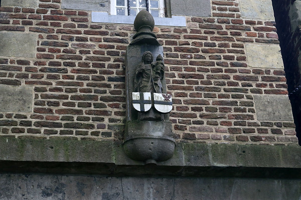 Sculpted statue and coat of arms upon the brick and stone wall at the Gemert Castle.
