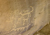 Petroglyphs pecked, incised, and abraded into the desert varnish (dark patina) upon the sandstone canyon wall of Chaco Canyon - Chaco Culture National Historical Park